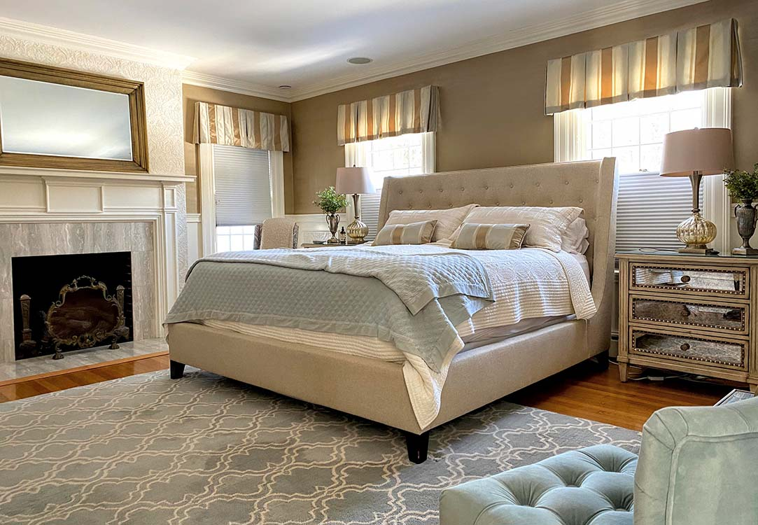 Large bed in master bedroom with fireplace