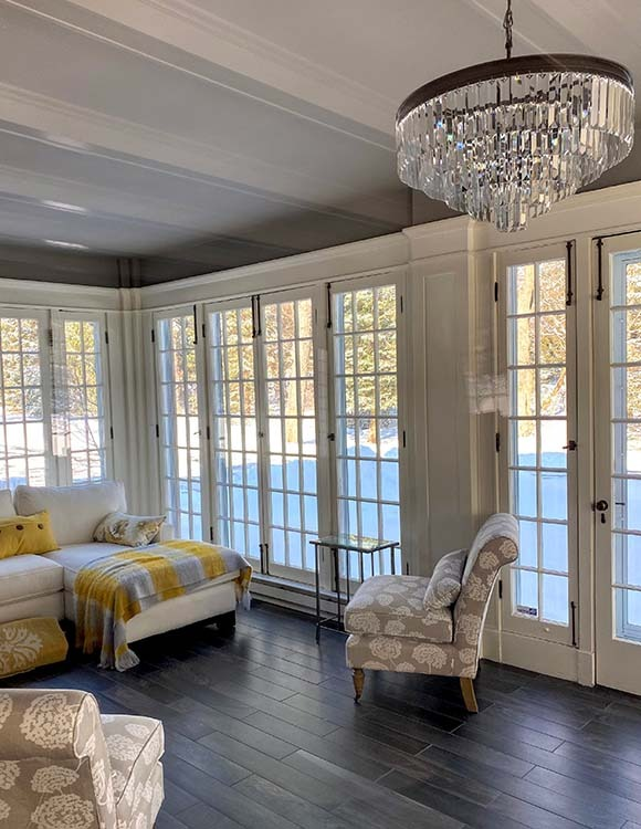 Sunroom with large doors and chandelier